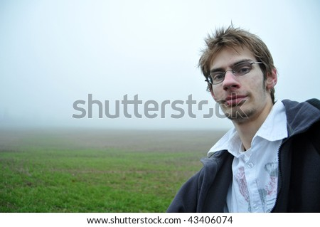 A young adult stands in a green foggy field looking at the camera with a smile. this makes a good background - stock photo