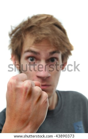 A young adult teenage man threatens with his clenched fist. The hand is selectively in focus. Isolated on white background - stock photo