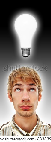A young adult white Caucasian teenage man looking directly above at a glowing light bulb. Professionally retouched. - stock photo