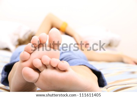 A young adult woman lying on the Bed. - stock photo