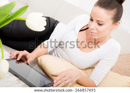 A young adult woman on the couch with a tablet.  - stock photo