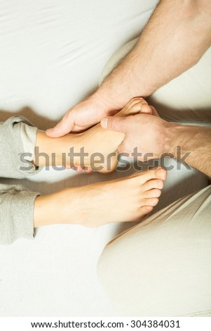 A young adult woman receiving a foot massage by a male masseur.