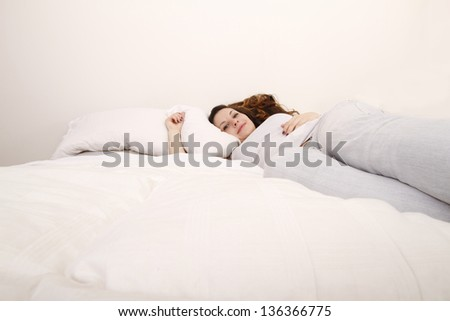 A young adult Woman relaxing on the Bed.