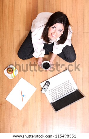 A young adult woman studying on the floor. - stock photo
