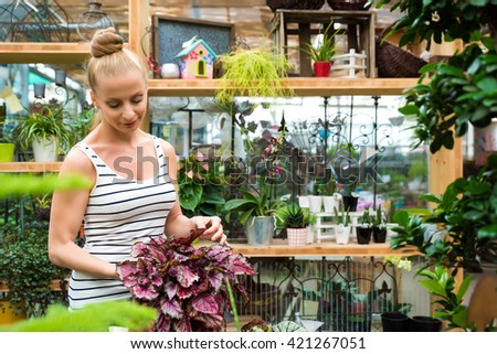 A young adult woman working in a gardening shop and carrying flowers - stock photo