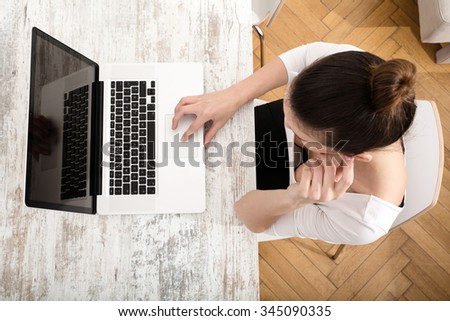 A young adult woman working on a laptop. - stock photo