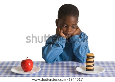 A young African American boy gets ready for a snack - studio shot isolated on white. - stock photo