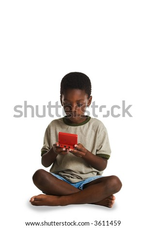 A young, African American boy playing an electronic game. This image is one of a series of conceptual images isolated on white backgrounds. - stock photo