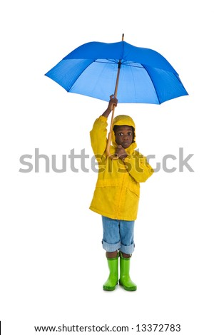 A young African American boy wearing a yellow rain slicker and carrying a blue umbrella. Isolated on a white background. - stock photo
