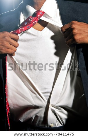 A young African American business man ripping his shirt open to reveal the t-shirt beneath. Add your text or artwork to easily customize the message. - stock photo