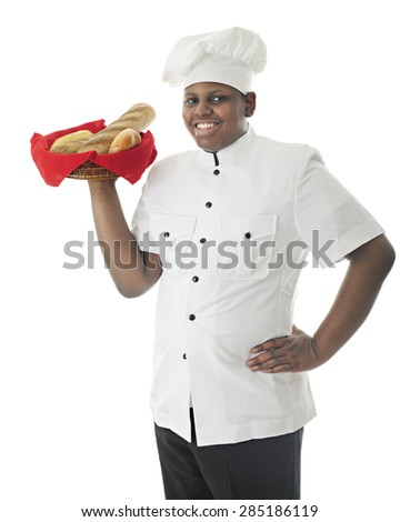 A young African American chef carrying a variety basket of breads over his shoulder.  On a white background. - stock photo