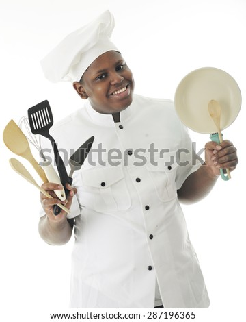 A young African American chef happily displaying some of his utensils and a small frying pan.  On a white background. - stock photo
