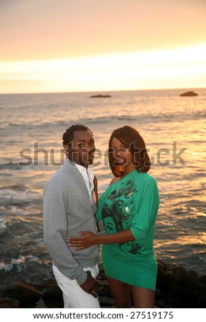 a young african american couple enjoy a sunset on the beach - stock photo