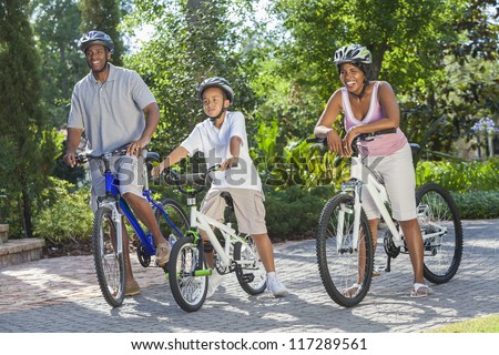 A young African American family, woman, man, father, mother & boy child riding bicycles in the summer - stock photo