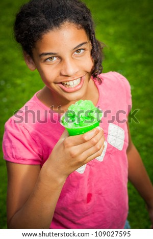 A young African-American girl holds a snowcone, smiling at the camera, outdoors. - stock photo