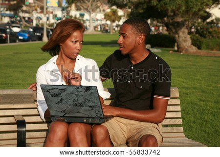 a young african american girl is upset at her boyfriend with what she finds while using a laptop computer outside - stock photo