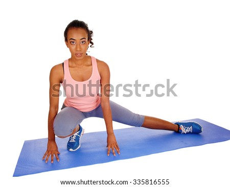 A young African American girl kneeling on a yoga mat, stretching her body,for fitness, isolated for white background. - stock photo