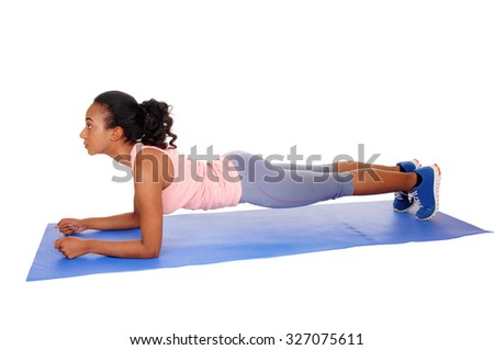 A young african american girl lying on a yoga mat, doing punch-ups, in bluetights, isolated for white background. - stock photo