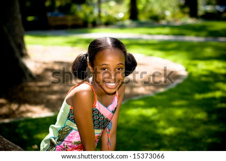 a young african american girl smiling - posed by a tree