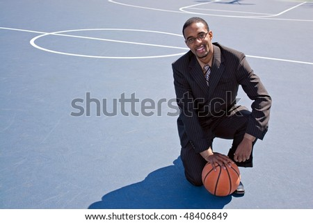 A young African American man in a business suit posing on the basketball court with a ball.  Works great for coaching or recruitment concepts. - stock photo