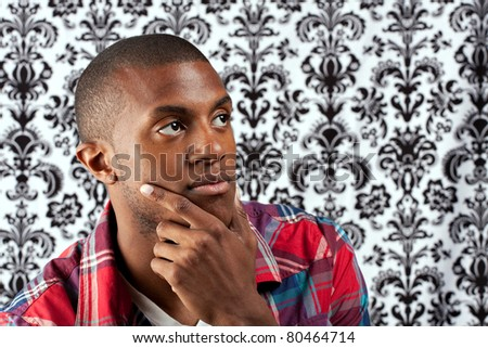 A young African American man in his twenties and his hand on his chin thinking deeply about something in front of a damask style background. Shallow depth of field. - stock photo