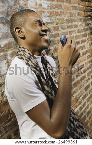 A young African American man on the phone in an urban environment. - stock photo
