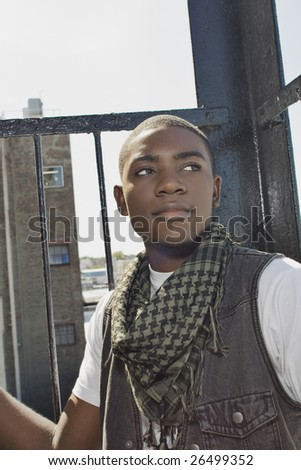 A young African American man sitting in an urban environment. - stock photo
