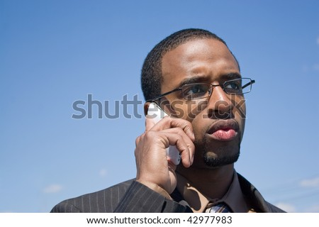 A young African American man talking on his cellular phone with a concerned or serious look on his face. - stock photo