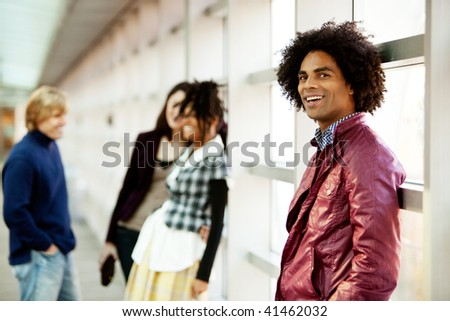 A young African American man with a group of people in the background - stock photo