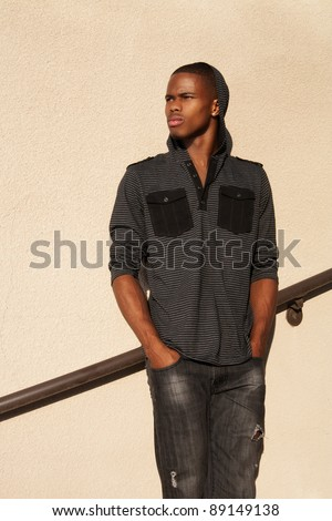 a young African American man with a hooded shirt stares off in the distance.