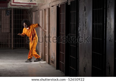 A young african american man with an afro is sneaking out of a prison cell. Vertical shot. - stock photo