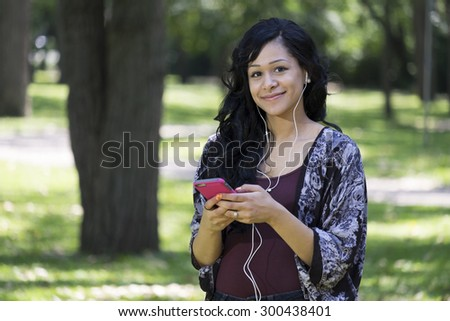 A young african american woman in a park wearing headphones and using a cellphone