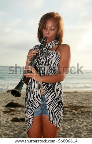 a young african american woman plays her clarinet outside at the beach for all to hear and enjoy - stock photo