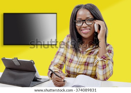 A young african american woman writing, and giving a call with mobile phone - stock photo