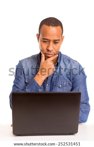 A young african business man working with a laptop - stock photo