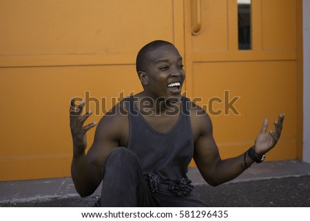 A young african man in front of a bright orange wall cannot believe his luck