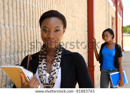 A young African teacher posed next to a wall with a student in the background out of focus. - stock photo