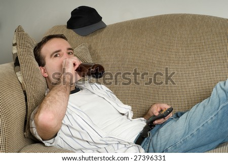 A young alcoholic lying on the couch drinking from a bottle of beer while watching tv - stock photo