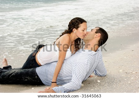 A young american couple are on the beach kissing, the woman is on top of the man - stock photo