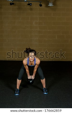 A young and athletic female trainer posing with a kettlebell in a gym doing a kettlebell swing. - stock photo