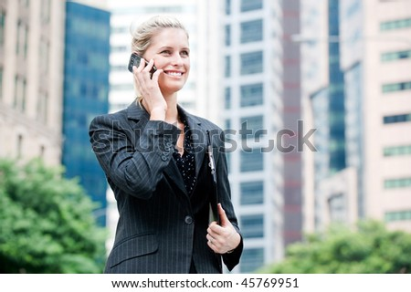 A young and attractive businesswoman using her mobile phone and holding a file under her arm - stock photo