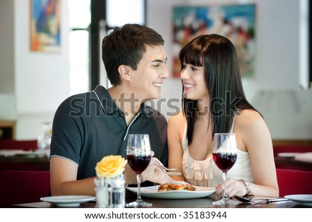 A young and attractive couple dining together in an indoor restaurant - stock photo