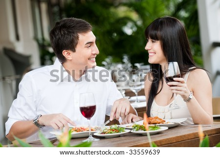 A young and attractive couple dining together in an outdoor restaurant - stock photo