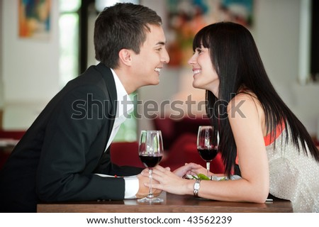 A young and attractive couple holding hands and about to kiss over their dinner in an indoor restaurant