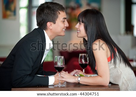 A young and attractive couple holding hands and about to kiss over their dinner in an indoor restaurant - stock photo