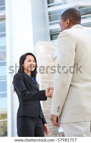 A young and attractive diverse business team handshake at office building