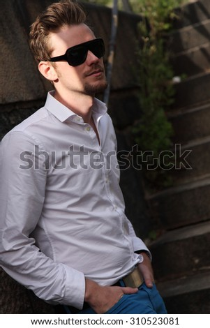 A young and attractive man in his 20s standing outside on a set of steps, wearing a white shirt, blue jeans and sunglasses, looking away from camera. - stock photo