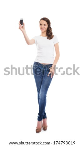 A young and attractive teenage girl with a mobile phone taking picture of herself isolated on white - stock photo