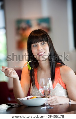 A young and attractive woman eating a salad in an indoor restaurant - stock photo