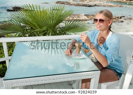 A young and attractive woman having a coffee break alone in an modern outdoor ocean view restaurant